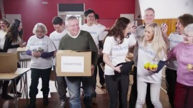 Large group of charity volunteers assemble and give big smiles into camera — Stock Video