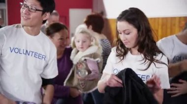 Beautiful charity worker accepts a can of food from cute little blonde girl — Stock Video