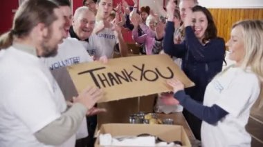 Charity volunteers give thumbs up to camera and hold up a Thank You sign — Stock Video