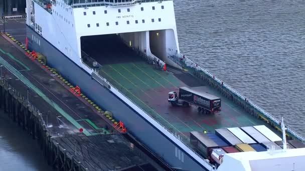 Camioneros maniobrar sus vehículos en posición sobre un barco de contenedores — Vídeo de stock