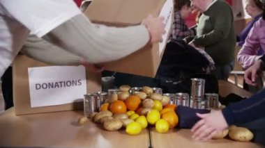 Charity volunteers and community members sort through donated food and clothing — Stockvideo