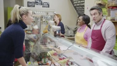 Friendly delicatessen staff serving customers with a smile at the cheese counter — Stock Video