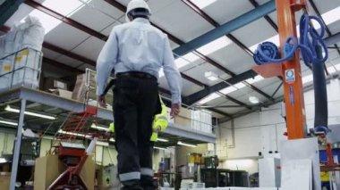 Werkneemster in een magazijn neemt instructies van haar managers — Stockvideo
