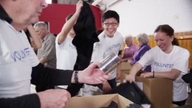 Charity volunteers of all ages enjoy a laugh and a joke together — Stock Video