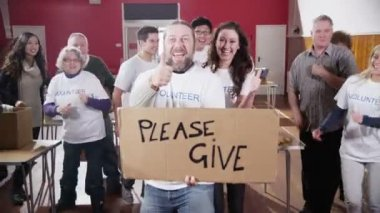 Group of charity volunteers give thumbs up to camera with a Please Give sign — Stock Video