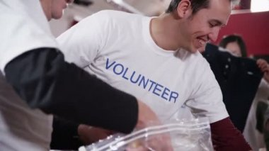 Charity volunteers of all ages smile as they're sorting through donated goods — Stock Video