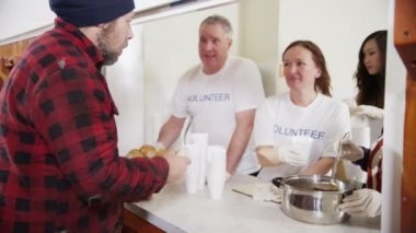 Soup kitchen volunteers help to feed the homeless — Stok video