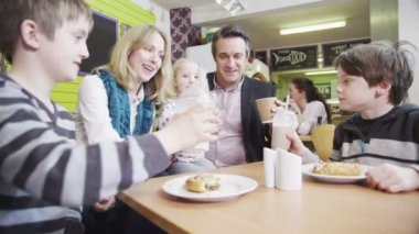 Happy affectionate family enjoying snacks and drinks in a cafe — Stock Video