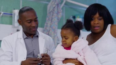 Male doctor uses a stethoscope to examine cute little girl in hospital. — Stock Video