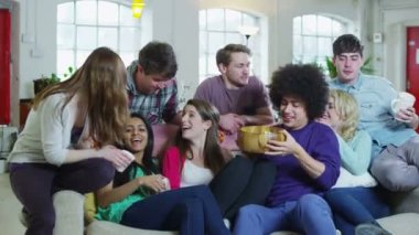 Happy group of friends relaxing on the sofa, eating popcorn and watching TV — Stock Video