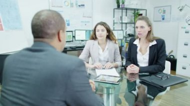 Businessman in a meeting gives good news to two of his staff — Stock Video