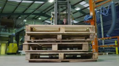 Team of busy warehouse workers lifting and moving empty wooden pallets — Video Stock