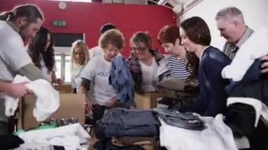 Charity workers and community members sort through donated food and clothing — Stockvideo