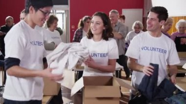 Charity volunteers sorting through donated goods — Stock Video
