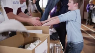 Cute young boy makes a charity donation and gets a high five from a volunteer — Stock Video