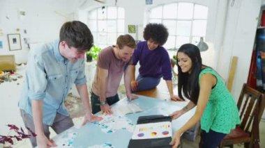 Studenten of jonge zakelijke partners werken samen aan een gezamenlijk project — Stockvideo