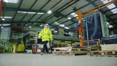 Team of busy warehouse workers lifting and moving empty pallets — Stock Video