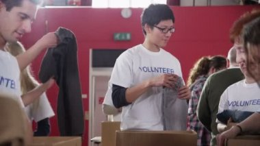 Charity volunteers in printed t. shirts sort through piles of donated clothing — 图库视频影像