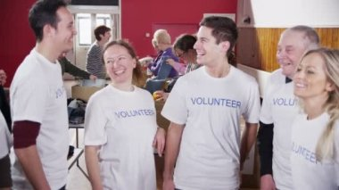 Happy circle of volunteers put their hands together in a show of unity — Stock Video