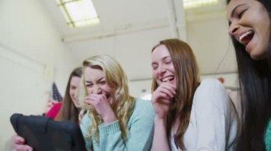 Glücklich lässig junge Freundinnen lachen, was sie, auf einem Tablet-Computer sehen — Stockvideo