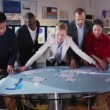 Attractive mixed ethnicity business team looking at a map of the world — Stock Video #45618353