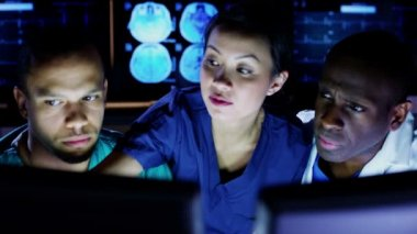 Medical team working late at a computer and discussing what they see on screen — Stock Video