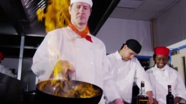 Professional chef in a commercial kitchen cooking flambe style. — Stock Video