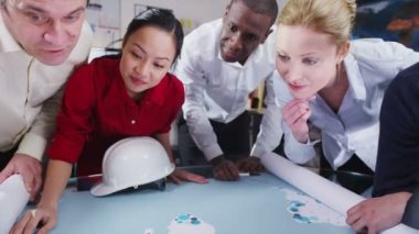 Cheerful mixed ethnicity team of architects or engineers looking at world map — Stock Video