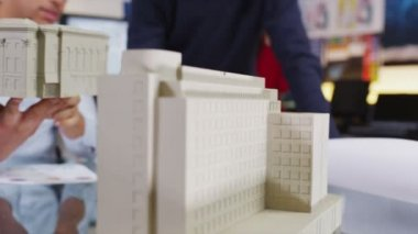 Two young architects or engineers looking at concept models of new development — Stock Video
