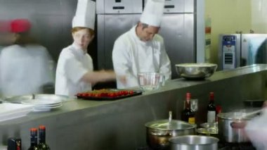 Busy team of chefs preparing food in a commercial kitchen — Stock Video