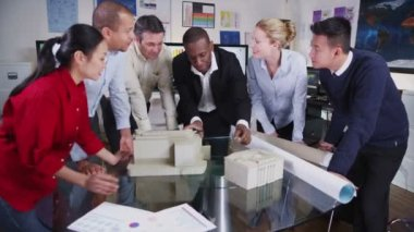 Mixed ethnicity team of architects looking at concept models of new development — Stock Video