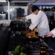 Team of professional chefs preparing and cooking food in a commercial kitchen. — Stock Video #45622771