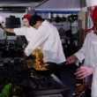 Team of professional chefs preparing and cooking food in a commercial kitchen. — Stock Video #45628403