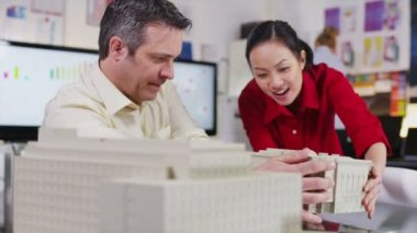 Cheerful architects or engineers looking at concept models of new development — Stock Video