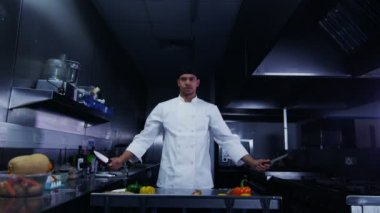 Serious chef in dark commercial kitchen holds knives above his head — Stock Video