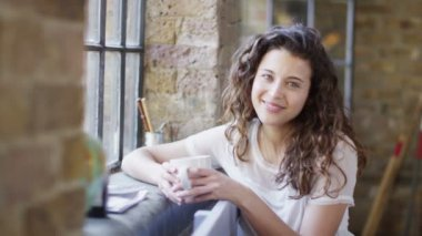 Woman sitting by window — Stock Video