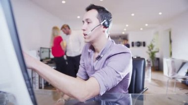 Young creative professional worker liaises with clients via a head set — Stock Video