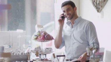 Ladenbesitzer macht Anruf am Arbeitsplatz — Stockvideo