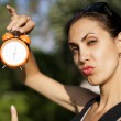 Foto Stock: Young womwith clock outdoors