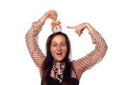 Joven mujer sostiene un reloj en la cabeza — Foto de Stock