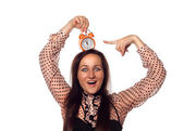 Young woman holding a clock on her head — Stock Photo