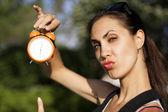 Młoda kobieta z zegarem na zewnątrz — Zdjęcie stockowe