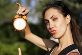 Young woman with clock outdoors — Стоковое фото