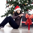 Stock Photo: Young womsitting near xmas tree with present