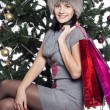 Stock Photo: Young womsitting near xmas tree with present after shopping d