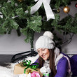 Young woman near xmas tree with presents — Stockfoto