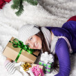Foto Stock: Young woman near xmas tree with presents