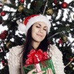 Pretty woman near christmas tree with present — Stock Photo