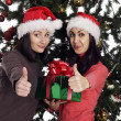 Two women near christmas tree with present showing hand ok sign — Stock Photo #38328605