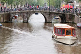 Pleasure boat moves through the channel in the heart of Amsterdam — Stock Photo